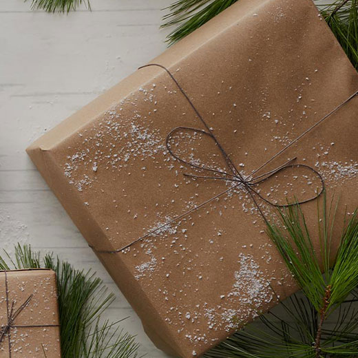 A brown paper-wrapped present with snow sprinkled on it, and green pine bows in the background.