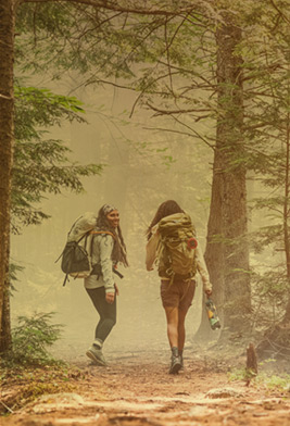 Two females with packs on, hiking happily down a trail in the woods.