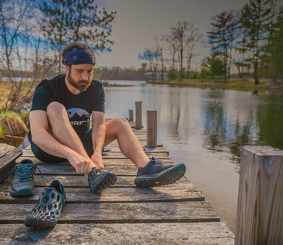 Man on a dock, switching shoes.