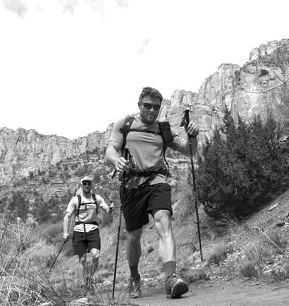 Two hikers heading up on a deep canyon trail.