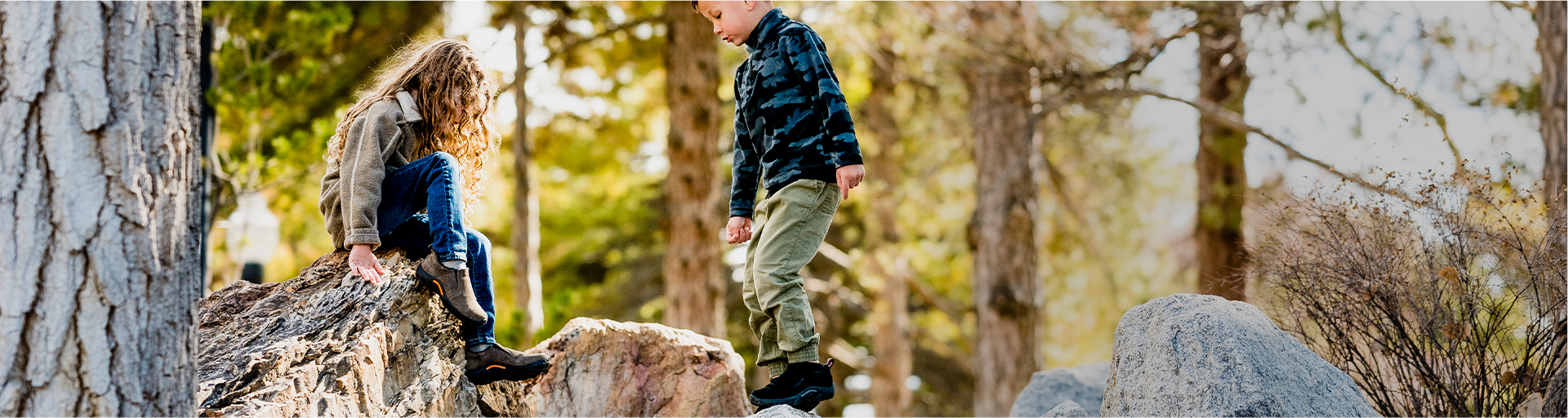 Kids playing in the woods while wearing Merrell shoes.