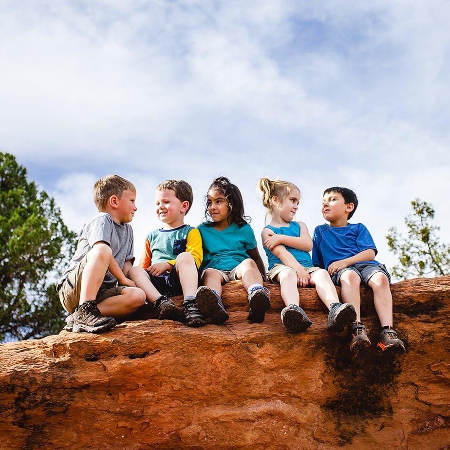 5 kids taking a rest on a rock during a hike