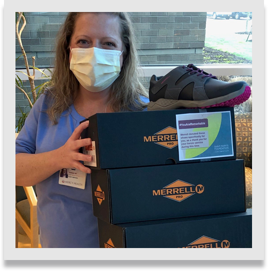 Nurse holding boxes of Merrell footwear.