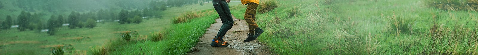 Two kids playing on a muddy trail in the rain.