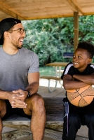 Guy sitting with a little kid holding a basketball and smiling.