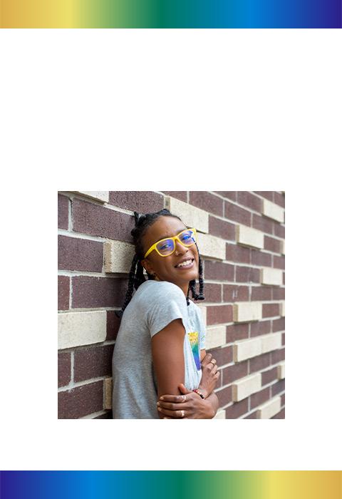 Latasha smiling while leaning against a brick wall.
