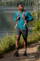 Person walking next to a lake with a Merrell backpack, looking cool.