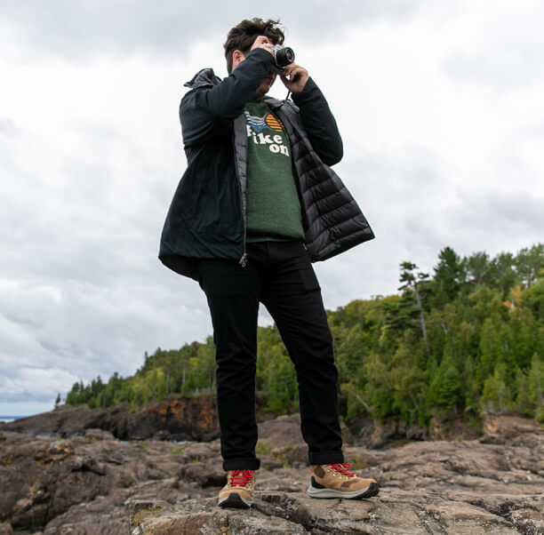 Standing on rocks, taking a photo with a camera.