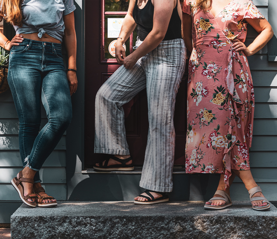 Women hanging out along a wall wearing Juno sandals.