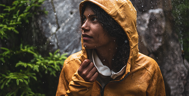 A man wearing a rain jacket while hiking.