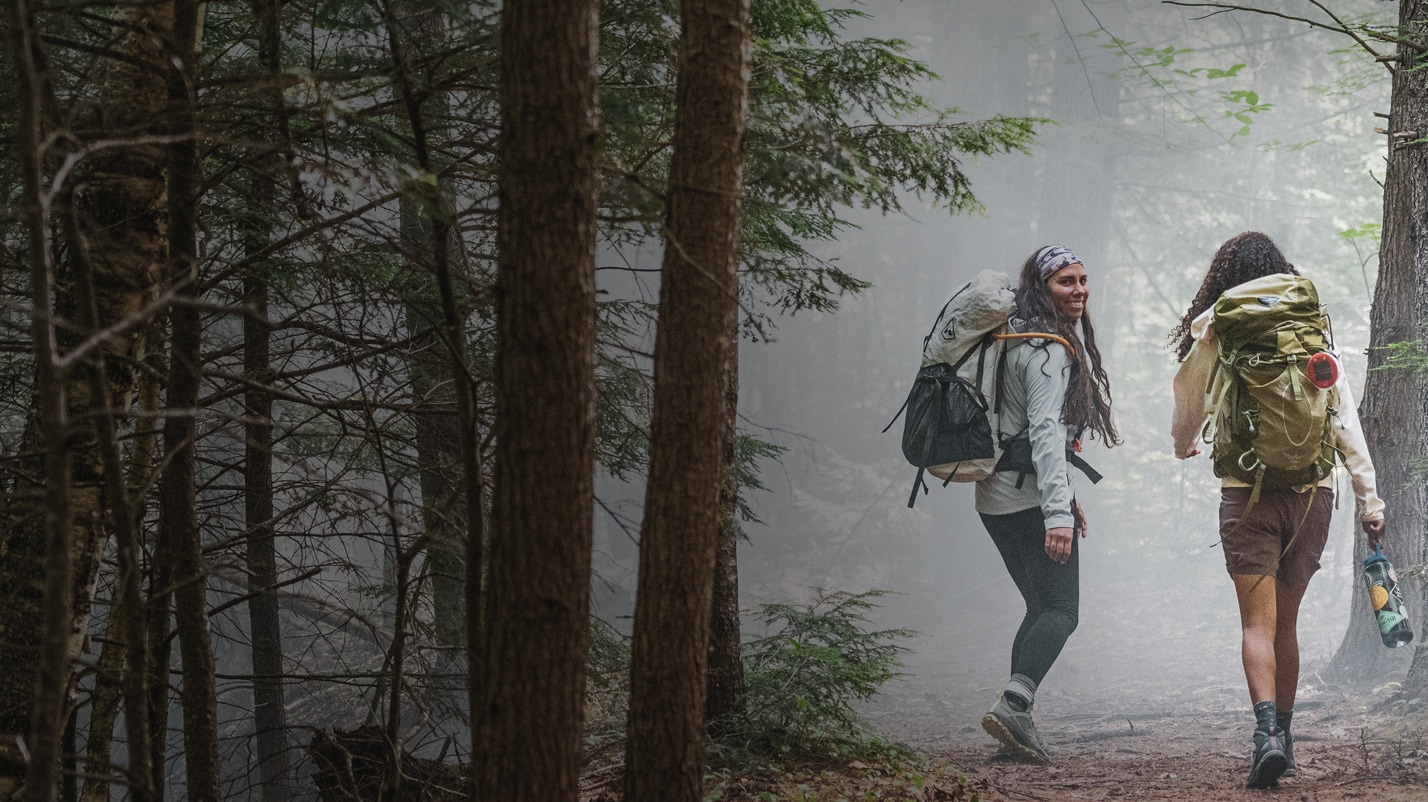 Two women backpacking in a foggy woods, wearing Merrell Bravada hiking shoes