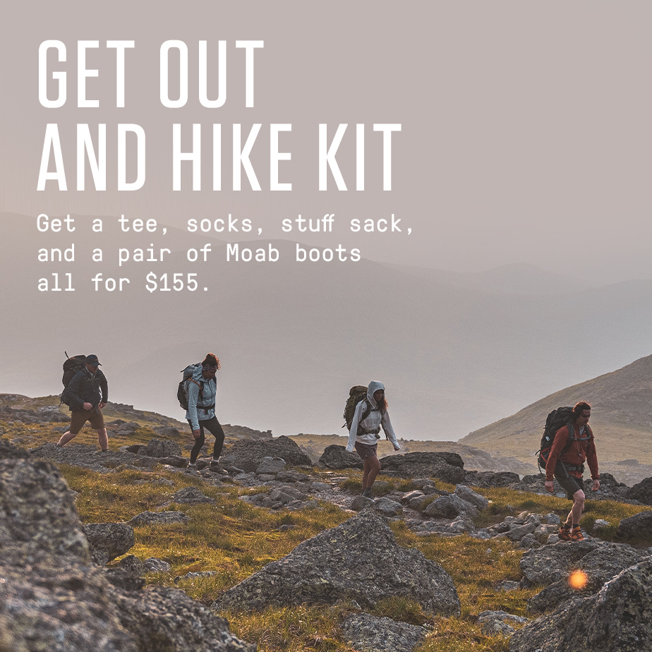 Get Out and Hike Kit - Get a tee, socks, stuff sack, and a pair of Moab boots all for $155. | Man running up a rocky mountainside wearing orange Skyfire shoes.