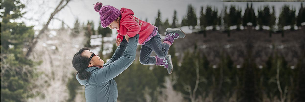 Mother lifting up her child outside in the snow.  Both are smiling and wearing Merrell hiking shoes.