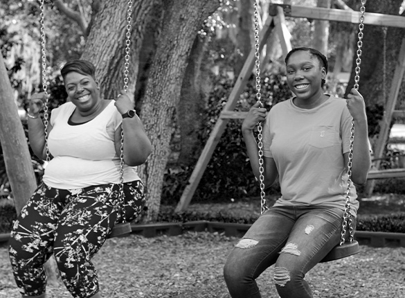 Child and adult sit on swings hanging from a tree, smiling at the camera.