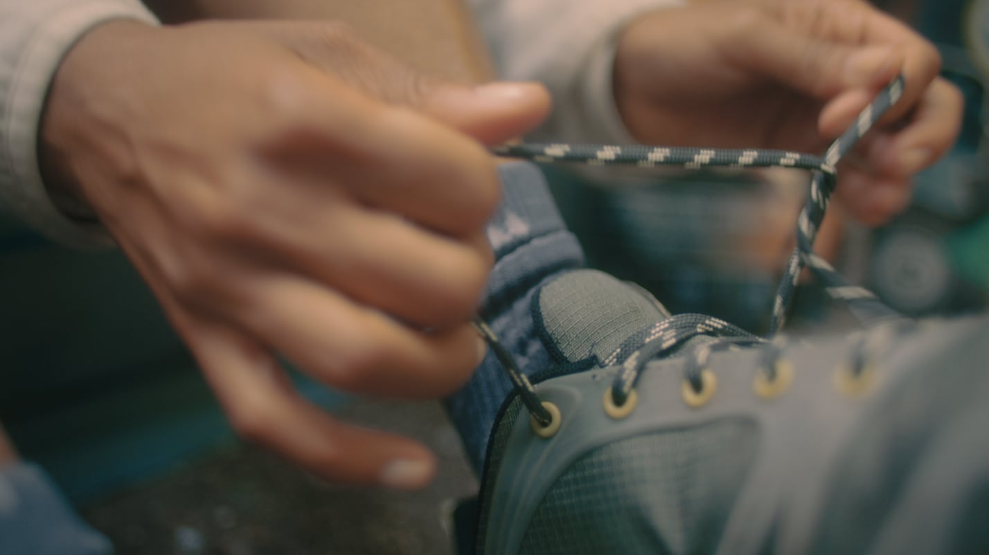A close-up shot of someone tying the laces of thier Merrell Altalight shoe