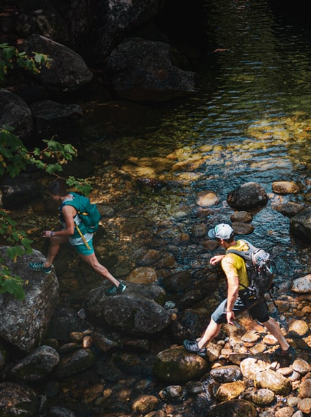Two people out for a hike, crossing a creek.