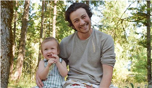 Benson Stewart, arm around his son in a forest.