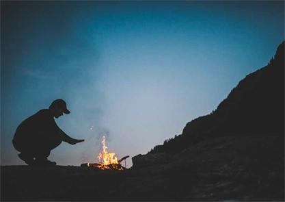 A man at a campfire at dusk.
