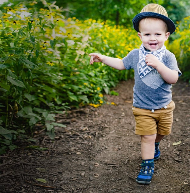 A cute baby hiking on a trail