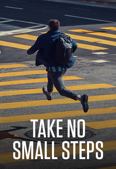 High-stepping it across a city crosswalk. Caption reads: Take no small steps.