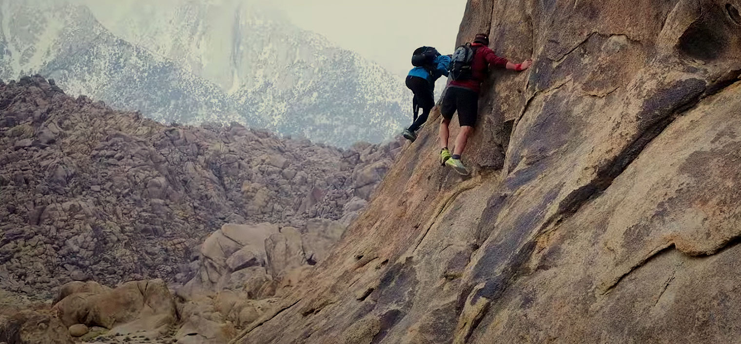 Two climbers scramble on a rock field.