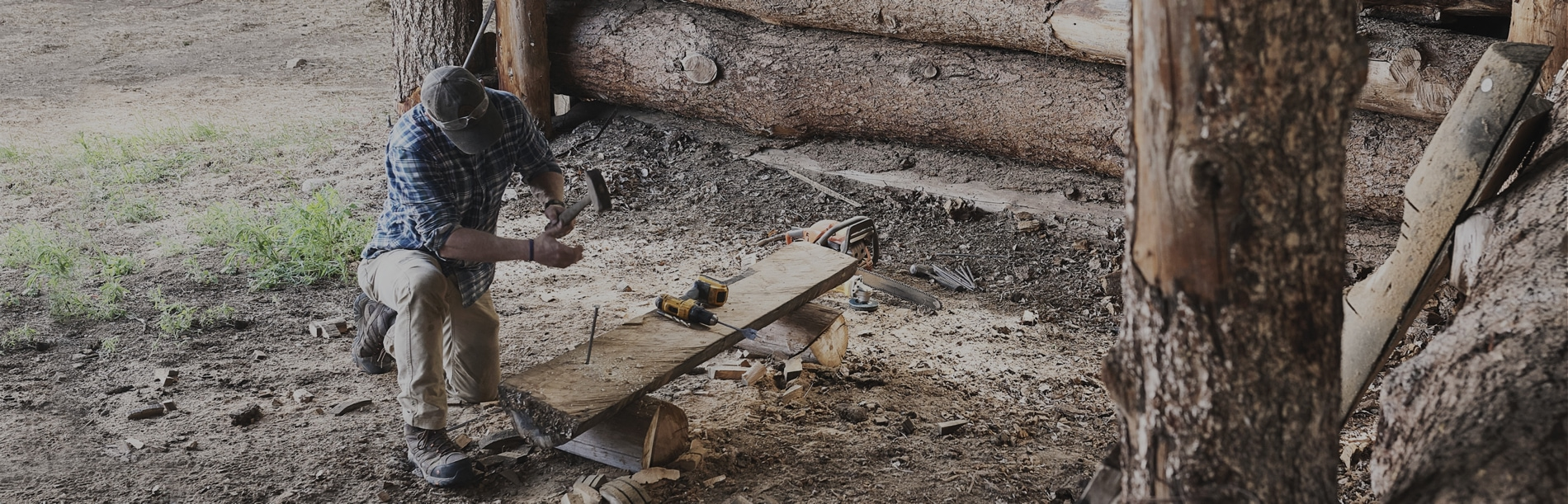 Person hammering in a large nail in a wooden bench, wearing Merrell Work Boots.